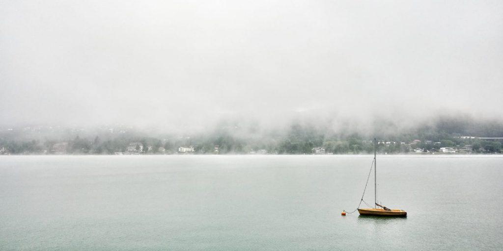 See der von Nebel umgeben ist mit einem angelegten Segelboot im Vordergrund